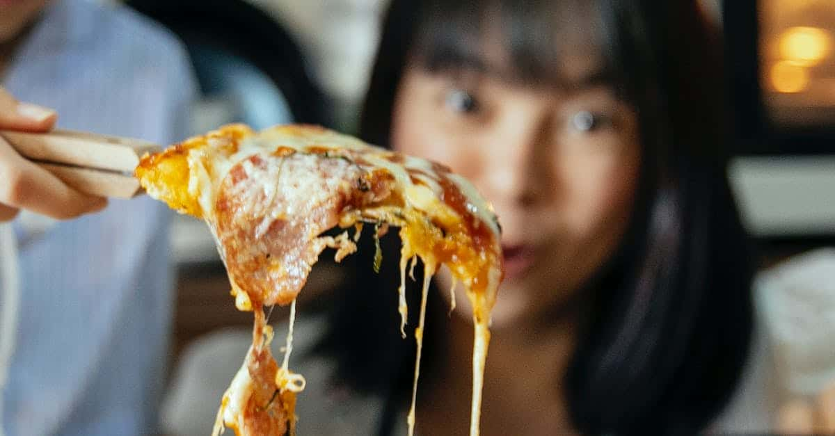 A close up of a person eating a slice of pizza